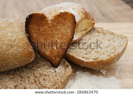 Protruding toast bread cut in the shape of hearts, with nature wooden background, white flour and cutted buns. Concept about love and bread. - stock photo