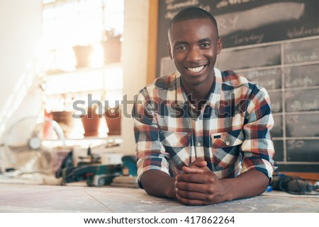 Proud African small busines owner in his beautifully lit studio - stock photo
