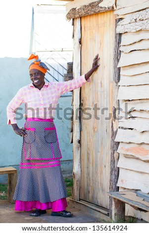 proud african woman leaning against her homes door smiling brightly - stock photo