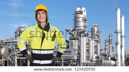 Proud and confident chemical engineer smiling into the camera in front of a petrochemical plabnt, with stainless steel crackers, destillation towers, and a couple of smoke stacks in the background - stock photo