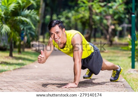 Proud and successful man doing sport push-up in tropical Asian park giving the thumbs-up sign