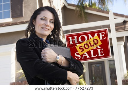 Proud, Attractive Hispanic Woman in Front of Sold Real Estate Sign and New Home.