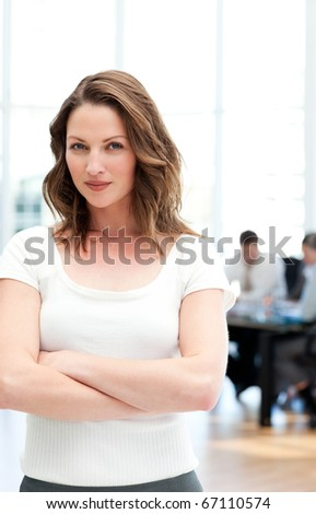 Proud businesswoman standing in front of her team while working in the background - stock photo