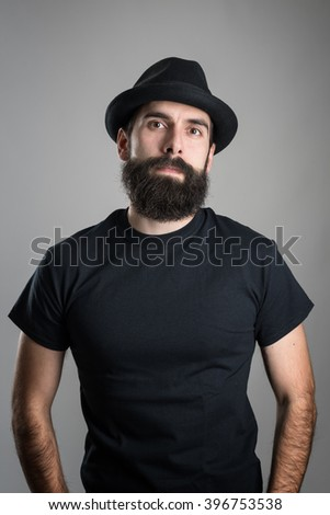 Proud confident bearded hipster wearing black t-shirt and hat looking at camera.  Headshot portrait over gray studio background with vignette.  - stock photo
