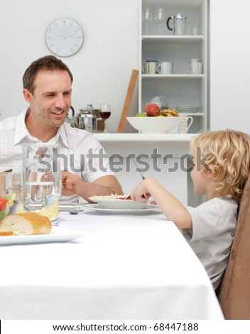 Proud dad talking to his son while eating pasta together in the kitchen - stock photo