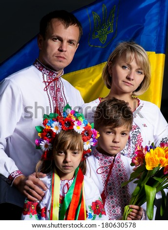 Proud family in the Ukrainian national costumes with Ukrainian flag - stock photo