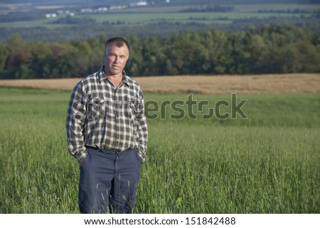 Proud farmer standing in one of his cultivated fields - stock photo