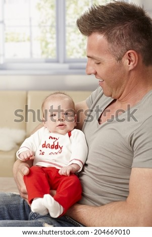 Proud father holding tiny baby in arms. My daddy is cool is written on baby's top. - stock photo