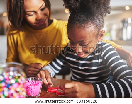 Proud female parent watching child fill heart shaped frame with little red beads on table in kitchen with soft sunlight pouring in - stock photo