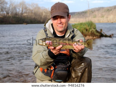 Proud fisherman posing with fish in a large river - rainbow trout - stock photo
