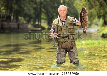 Proud fisherman standing in a river and holding a fish and a fishing rod - stock photo