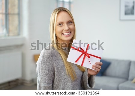 Proud happy attractive young blond woman holding a festive envelope tied with a red ribbon displaying it to the camera as she stands in her living room at home, conceptual image - stock photo