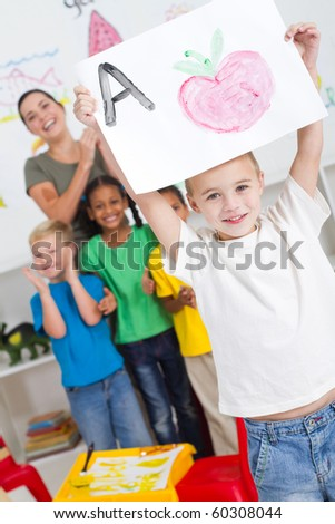 proud kindergarten boy holding painting high - stock photo