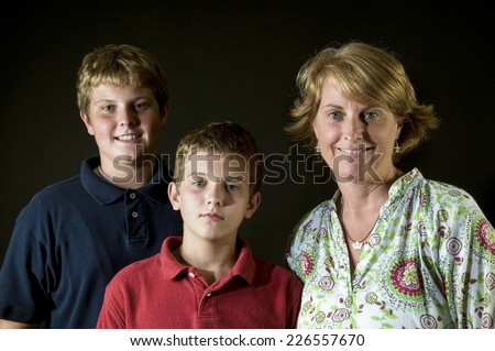 Proud Mom with sons, ages thirteen and eleven, with different expressions - stock photo