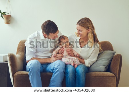 Proud mother and father smiling at their newborn baby daughter, sitting on the sofa at home - stock photo