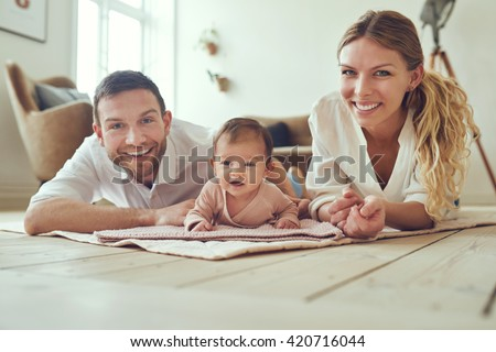 Proud mother and father with their newborn baby daughter, lying on the floor at home - stock photo