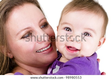 Proud mother looking at  smiling eight months old baby. Baby have a surprized happy look.