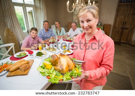 Proud mother showing roast turkey at home in the living room