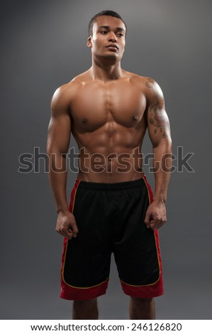 Proud of his fit body. Young shirtless African man looking away wearing basketball shorts while standing against grey background  - stock photo