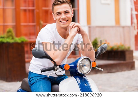 Proud of his new scooter. Handsome young man sitting on scooter and smiling  - stock photo