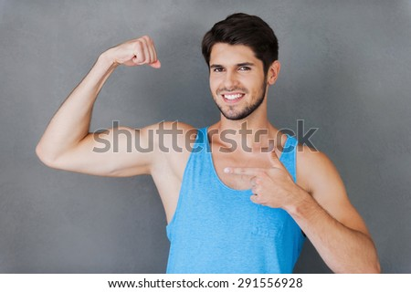 Proud of his perfect biceps. Cheerful young muscular man pointing his bicep while standing against grey background - stock photo