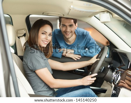 Proud of their new car. Beautiful young couple are examining a new car at the dealership - stock photo