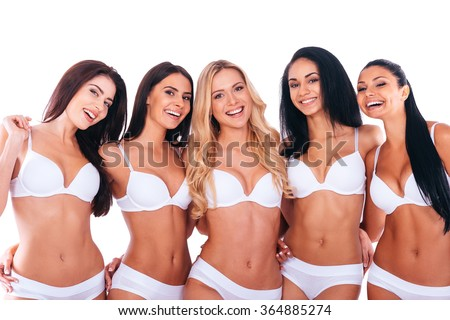 Proud of their shape bodies. Group of cheerful beautiful women in lingerie bonding to each other and smiling while standing against white background - stock photo