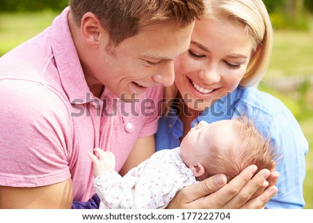 Proud Parents Holding Baby Daughter In Garden - stock photo