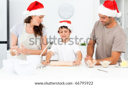 Proud parents looking at their son using a rolling pin in the kitchen at home - stock photo