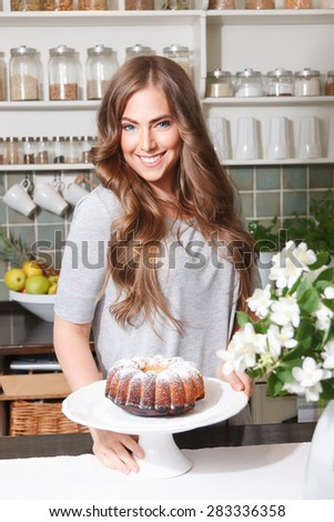 Proud pretty woman with a homemade cake - stock photo