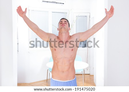 proud shirtless man in winning pose with hands up, serious young sexy muscular macho man posing in naked torso holding raised hands and arms up, man winner with athletic sport body raising hands - stock photo