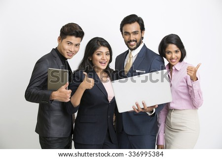 Proud smiling businessman standing with his colleagues showing thumbs up on white. - stock photo