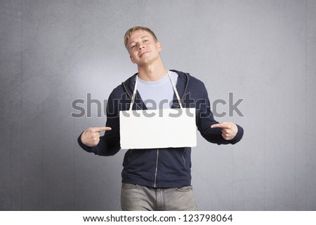 Proud smiling man pointing fingers at white blank signboard with space for text isolated on grey background. - stock photo