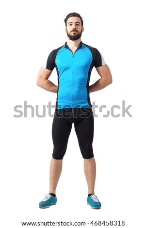 Proud strong sporty cyclist in cycling clothes standing with hands hands behind back. Full body length portrait isolated over white studio background.