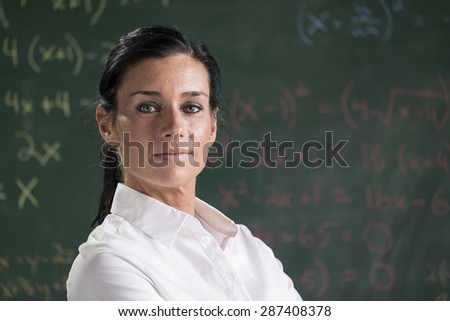Proud teacher in front of chalkboard - stock photo