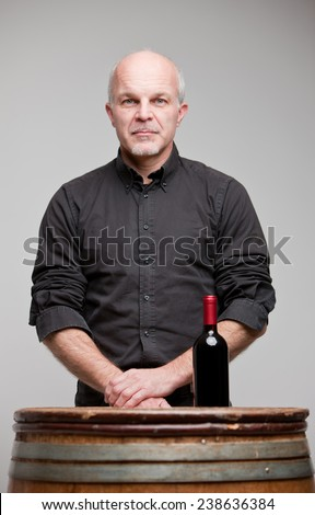 proud wine maker man with a bottle of excellent red wine - stock photo