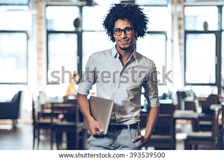 Proud with his small business. Young cheerful African man carrying laptop and looking at camera with smile while standing at cafe - stock photo