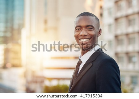 Proud young African business entrepreneur smiling in a city - stock photo