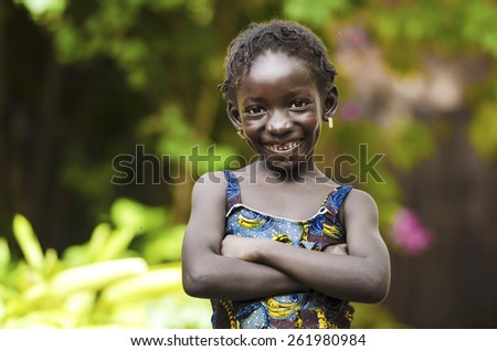 Proud Young African Girl Posing with Arms Crossed.  In the streets of Bamako, an African teenage girl is posing for the camera. - stock photo