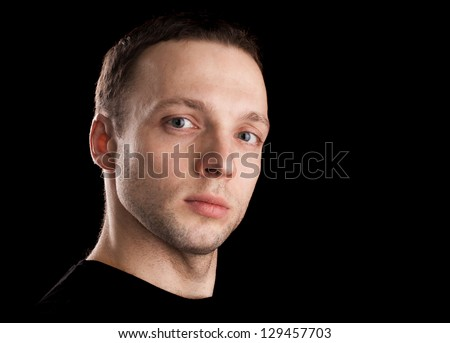 Proud young Caucasian man's portrait. Close-up face shoot isolated on black
