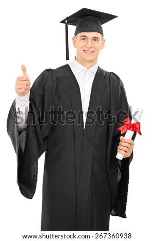 Proud young college graduate in a graduation gown holding a diploma and giving a thumb up isolated on white background - stock photo