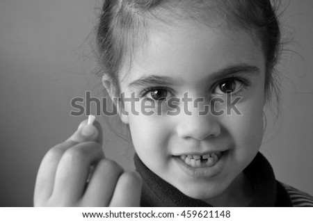 Proud young girl (age 6) holds her first falling milk teeth, looks at the camera. Childhood healthcare concept. real people copy space (BW) - stock photo