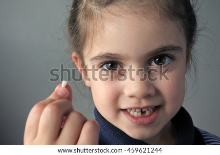Proud young girl (age 6) holds her first falling milk teeth, looks at the camera. Childhood healthcare concept.real people copy space - stock photo