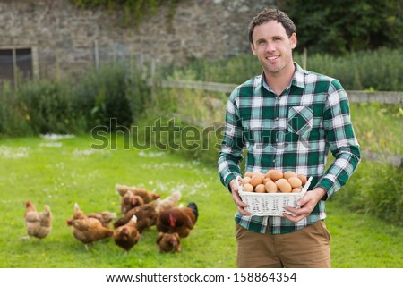 Proud young man holding a basket filled with eggs with chickens behind him - stock photo