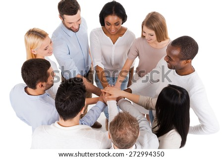 Proudly successful team. Top view of positive diverse group of people in smart casual wear keeping their hands clasped and smiling while standing close to each other