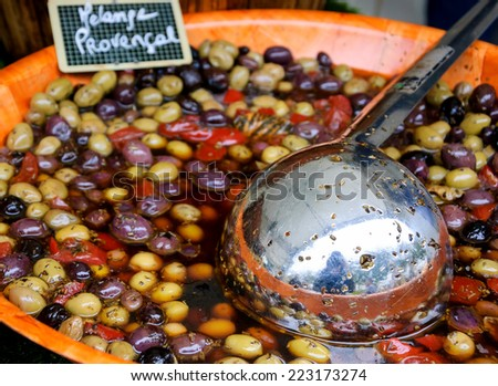 "Provencal Mix of Olives (""Melange Provencal"" in French) ) in wooden bowl at the food market in Paris. Selective focus. - stock photo"