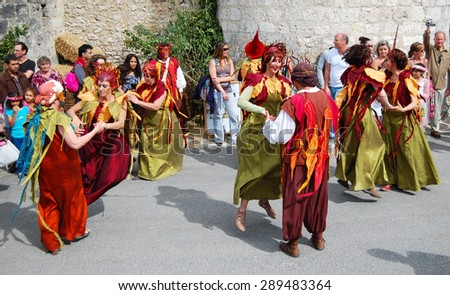 PROVINS, FRANCE - JUNE 23, 2012: People dancing and whirling in elf colorful costumes during the traditional Medieval festival. Medieval town of Provins is UNESCO World Heritage Site. - stock photo