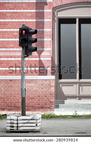 Provisional traffic light behind a temporary brick wall painted canvas. Trompe l'oeil. - stock photo