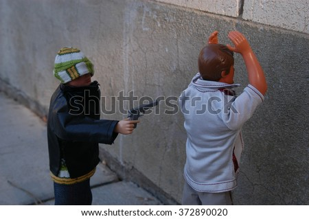 Provo, Utah, USA - 4 December 2004:  Vintage Gi Joe and classic Ken doll illustrate gun violence in US.  Thief points a hand gun at the victim, demanding money and wallet. - stock photo