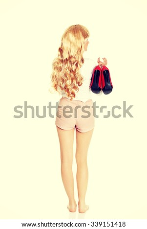 Provocative blonde woman holding her high heels in hand. - stock photo